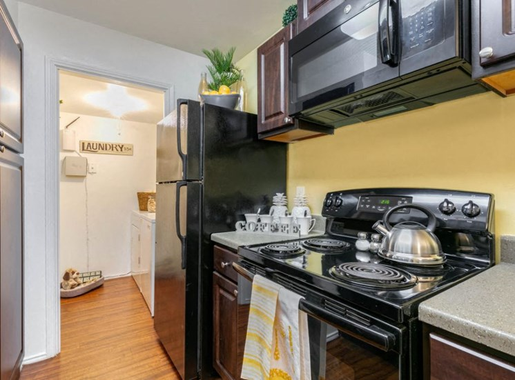 Fully Equipped Kitchen with Black Appliances and Brown Cabinets